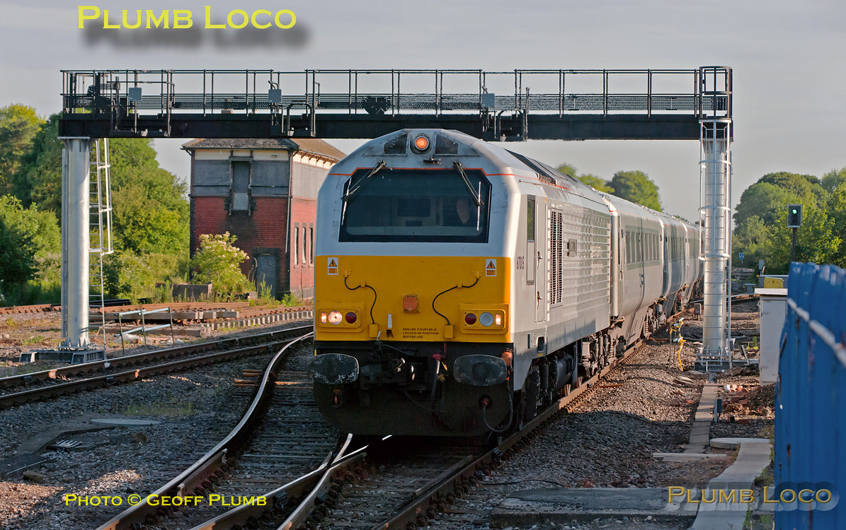 """Former W&S 67015 """"David J. Lloyd"""" heads 1H06, the 05:43 from Birmingham Moor Street to Marylebone, into Princes Risborough passing the newly installed signal gantry to the north of the station. The stanchions for this appeared a week or so earlier and the crossbeam was put into place over the Bank Holiday weekend of 28th to 30th May 2011. Once the signals themselves have been installed and commissioned, they will control northbound moves from the station on all three main tracks. 07:06, Wednesday 1st June 2011. Digital Image No. GMPI9345."""