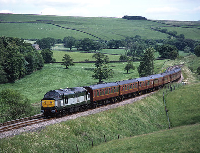 Unique liveried 37197 hauls a York-Carnforth empty stock move through the lush summer greenery at Eldroth 13/6/04.