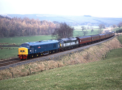 Tragically missing the sun, 45112 hauls 37197 and empty stock from Barnetby-Carnforth past Eldroth 20/3/05.