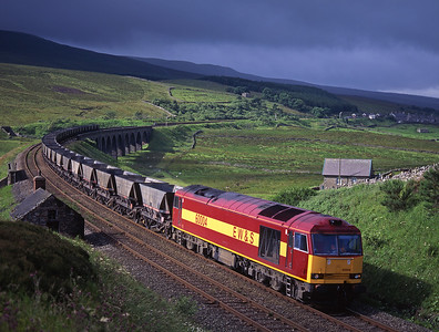 On a morning of changeable weather 60004 crosses Dandry Mire with coal empties, 13/7/98.
