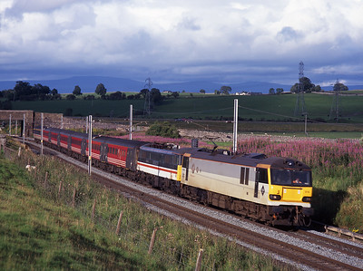 Possibly the first ever class 92 hauled service train, 92019 hauls failed 86225 on 1O16 at Shap Beck on 21/8/98.