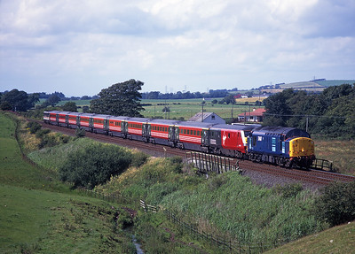 Over the weekend of 1-2 August 1998 there were unplanned diversions over the GSW using a variety of motive power.  On the Sunday 37607 hauls 1M35 near Cummertrees with 87014 on the rear.