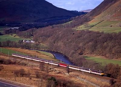 "87025 ""County of Cheshire"" hauls a Glasgow-Euston train through the Lune  Gorge on 22/2/98.."