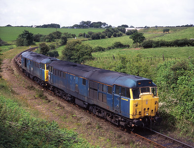 31434 + 31450 pass Thwaite Flat with barrier wagons for Sellafield on 11/7/98.