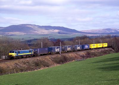 "90128 ""Vrachtverbinding"" hauls an intermodal train past Hayfell on 14/3/98."