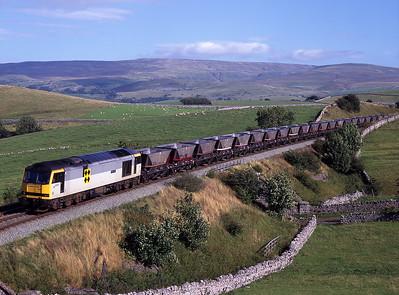 "On Sunday 7/9/97 60057 ""Adam Smith"" passes Waitby with coal empties."