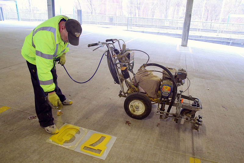 There is minor work left to be done at the parking garage at the Leominster train station. They say it will be open very soon.  Brent Brown owner of BNB Pavement markings works on painting the numbers for the parking spaces on Tuesday morning. SENTINEL & ENTERPRISE/JOHN LOVE