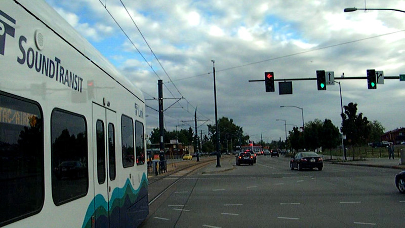 An outbound Central Link train departs Othello station and crosses an intersection as it accelerates on its run to the SeaTac airport on 10-9-11.