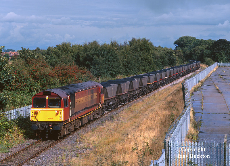 58039 passes Southcoates Lane, Hull, at 15:23 on Saturday 12th September 1998, with the 7C02 15:30 Hull Coal Terminal - Eggborough Power Station. <br /> The dark sky and puddles adorning the former timber yard would suggest that I had been extremely lucky to catch this one in sunshine!