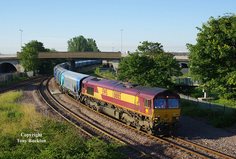 66165 takes the branch to Hull Docks at Hessle Road Junction at 06:41 on Monday 7th July 2014 with the 04:30 empty Biomass hoppers from Drax Power Station. <br /> The train running approximately 30 mins late resulted in a shot with much reduced shadows from the buildings just out of shot on the left.