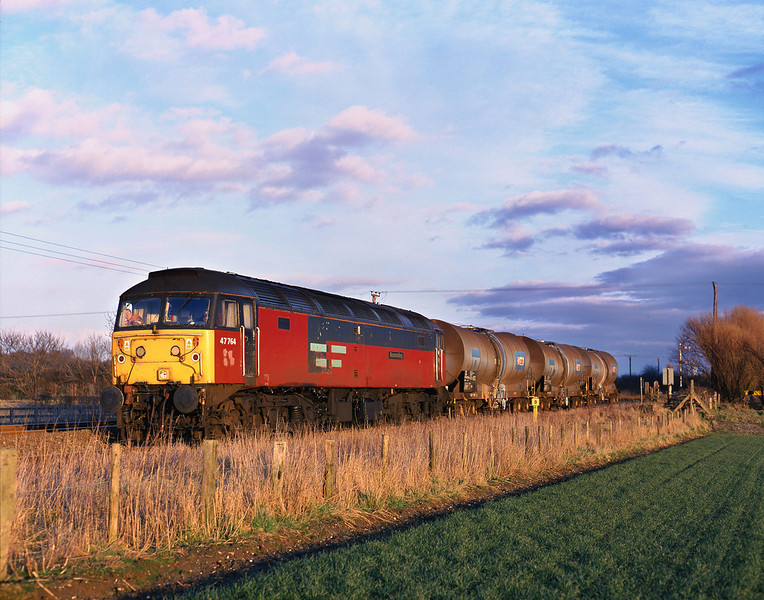 In the last rays of sunlight on Friday 19th February 1999, 47764 waits for clearance from the signaller at Melton Lane to set back into the premises of Croxton & Garry to exchange Calcium Carbonate slurry tanks, before continuing with the late running 6D54 13:56 Hull - Doncaster Enterprise.