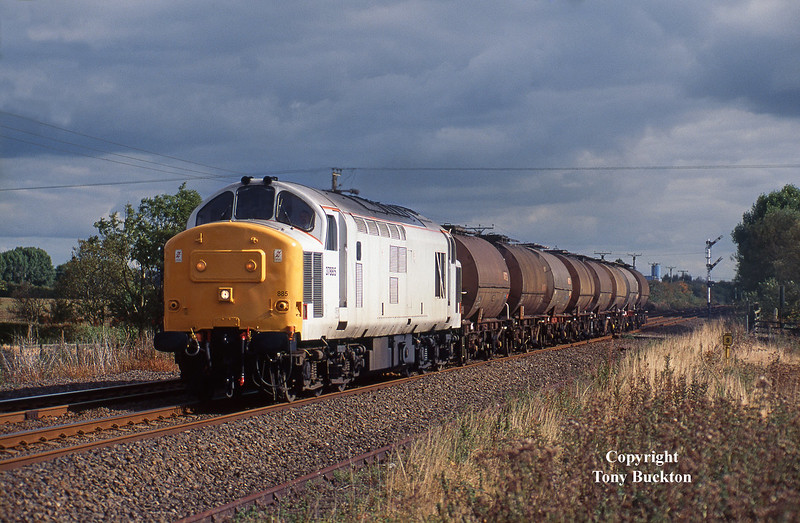 With the bright ghost livery of the loco contrasting against a threatening sky on Saturday 5th October 1996, 37885 passes Lowfield Lane, Melton, with the Saturdays Only 6D62 12:12 Saltend – Healey Mills acetic acid tanks for Mostyn Dock. <br /> Despite the launch of EW&S maroon and gold in the late April of this year, 37885 was surprisingly dispatched from Brush Traction in undercoat on the 2nd May 1996.