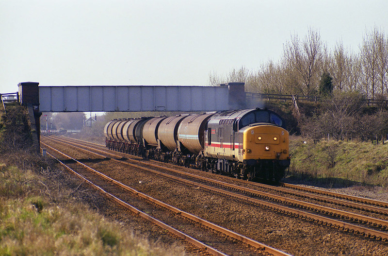 37405 passes under Brickyard Lane, Melton, with the 6E39 Mostyn Dock - Saltend at 13:30 on 26th March 1993.