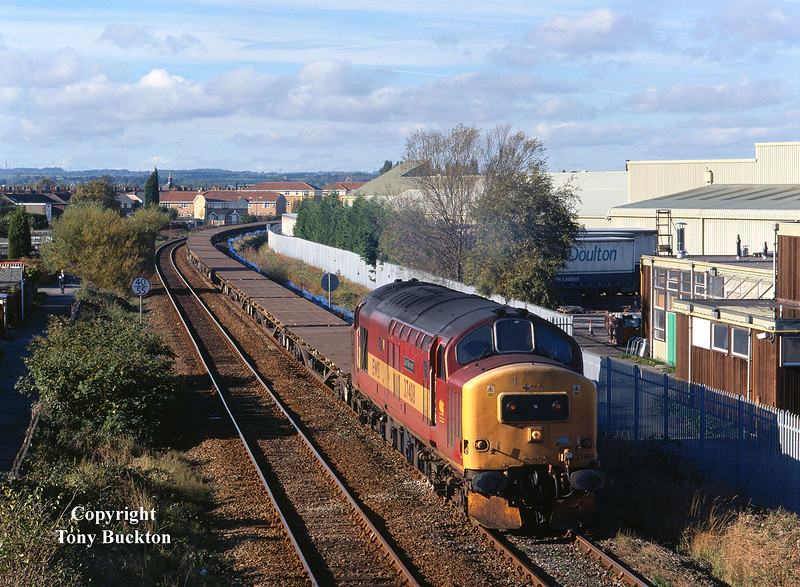 37408 passes the works of Ideal Standard, Hull, with a long rake of 'Salmon' track panel wagons forming the 6T66 Nafferton - Doncaster engineers trip, at 12:32 on Sunday 28th October 2001.