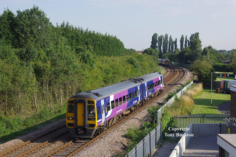 158815 is about to pass under County Road flyover, Hull, forming the 2W36 16:44 Hull - Bridlington on Saturday 22nd August 2015.<br /> A photograph at this location has not been possible for many years due to vegetation - in fact for as long as I can remember (and I've lived a few mins walk away for most of my 46 years!). The area to the left of the remaining tracks once held the exchange sidings for the works of Hull Radiators (still in existence as Ideal Standard). This was also the site of Cottingham South Junction, from which a direct line diverged straight ahead (to the right of the poplars) to form a direct route out of Hull via Hessle Rd Jnc - the box that controlled the junction would have been situated in the right foreground.