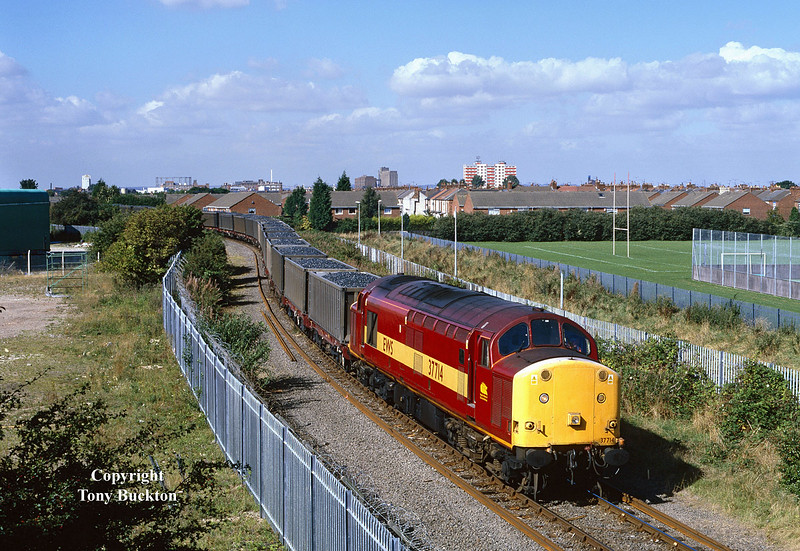 37714 passes Southcoates Lane, Hull, shortly before arriving at King George Dock on Thursday 9th September 1999.<br /> Running as 6G89 Doncaster - Hull King George Dock, this train of loaded Russell's coal containers had originated from Swansea Burrows the previous day, and was unusual in running mid-week - a Saturday morning arrival was the norm during the short period in which these services ran on behalf of Celtic Energy.