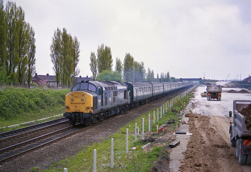 On the morning of May 17th 1984 I was at Hessle from just after 07:00 awaiting D200 (40122) with the Hull - York Speedlink, when 37283 passed ahead of it with withdrawn Trans-Pennine stock, which is thought to have originated from Hull Dairycoates as this is where the sets had been stored following displacement - I've no idea where they were heading.<br /> This photo was scanned from a poor quality 35mm negative, and whilst far from great, has been included for historical value.<br /> The building works to the right of the picture are the foundations of the main A63 (Clive Sullivan Way) access road into Hull, which was in the process of being built at the time - this totally destroyed the tranquillity of the area.