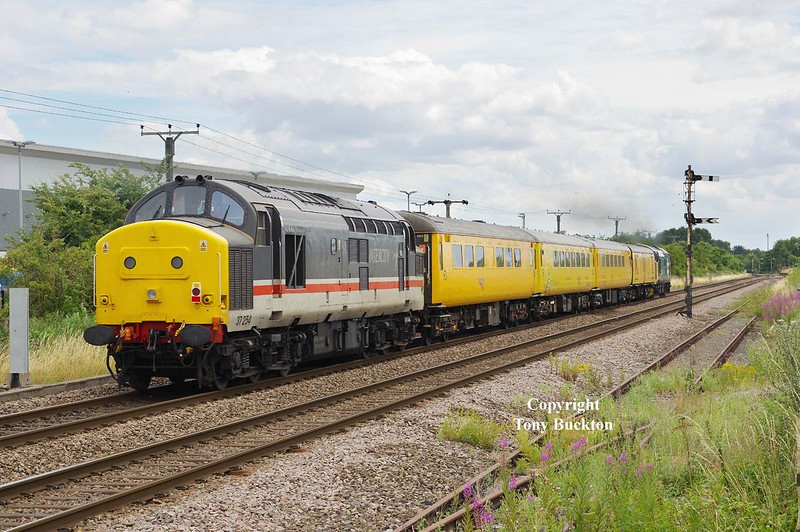 """37025 heads for Hull Paragon seen passing Lowfield Lane Melton at 12:44 on Monday 25th July 2016 with the 09:52 Derby R.T.C. - Derby R.T.C. test train. 37254 brings up the rear.  37025 was photographed at this location almost 18 years earlier but heading in the opposite direction - see link; <a href=""""https://tonybuckton.smugmug.com/Trains/Class-37s-through-the-ages/i-J5kF5ZC"""">https://tonybuckton.smugmug.com/Trains/Class-37s-through-the-ages/i-J5kF5ZC</a><br /> The intervening years have had mixed fortunes for this view in that the rural feel has been spoilt by the Heron frozen food distribution centre which now dominates the background - However, as a plus,  the tall trees to the right (South) of the shot have been removed leaving the location shadow free."""