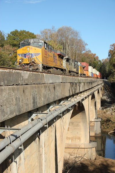 23N-06 [Intermodal; Atlanta, GA-Memphis, TN]<br /> NB UP 5532 (AC4400CTE, flag)<br /> <br /> NS 4004 (AC44C4M, Lion's Mane Primer Fish Paint)<br /> UP 6868 (AC4400CW, flag)<br /> <br /> 86 platforms intermodal (25 international intermodal, 61 domestic<br /> doublestacks). Shot crossing Sweetwater Creek. #2 to runaround at NS Austell,<br /> Austell, GA. Since 25Q originated in Atlanta today instead of Savannah, these<br /> were back to back Atlanta-Memphis intermodals!