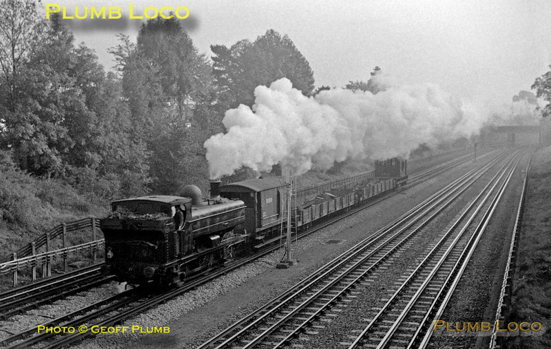 An unidentified LT 0-6-0PT is working the spoil train from Neasden to Watford and the tip at Croxley, passing Pinner Green on the down slow line. Exact date not recorded, but around June 1968.