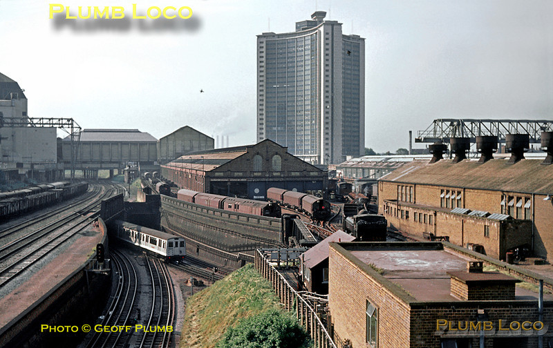 General view of Lillie Bridge depot as seen from the West Cromwell Road bridge in June 1969. On the left are the tracks of the West London Extension Joint line (GWR, LNWR, LSWR & LBSCR Joint) with the sidings full of wagons overshadowed by the bulk of the Earls Court exhibition centre. A District Line train which has just left West Kensington station for Earls Court is diving under these tracks at what was known as West Kensington East Junction, now Olympia Junction, the low level lines in the foreground heading to Olympia. In the centre, London Transport ex-GWR 0-6-0PT No. L95 is propelling a works train into the yard of the depot, having just arrived from the Addison Road direction (now Kensington Olympia), while various Battery Electric locos stand around between duties. The four chimneys of the Power Station which was close by Wandsworth Bridge can be seen in the distance. This whole area is transformed today, much of it covered by the extension to the Earls Court exhibition complex, though some of the depot tracks are still in use!