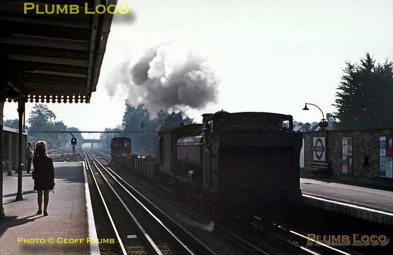 The fireman keeps an eye on the injector overflow as LT 0-6-0PT No. L99 (ex-GWR & BR No. 7715) passes through Pinner station with the northbound spoil train from Neasden to Watford and the tip at Croxley, October 1969. Slide No. 4184.