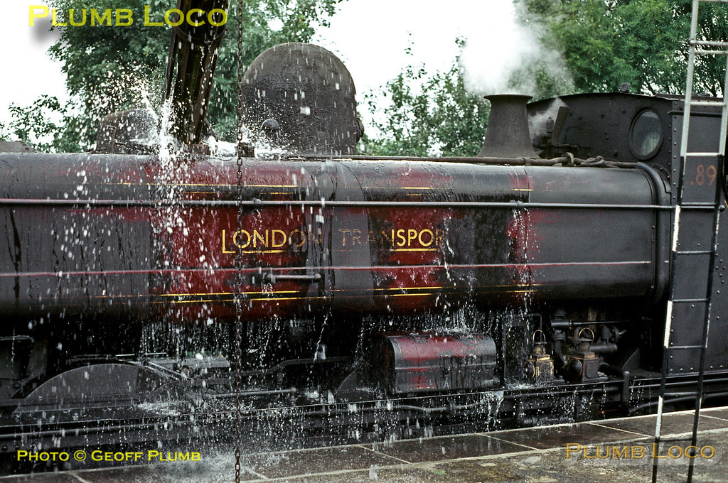 In a scene that explains the pattern of clean patches on the tanks of LT 0-6-0PT No. L89, the engine is being watered at Watford station rather over-enthusiastically, the water cascading down the sides and cleaning as it goes! The engine has arrived with the spoil train from Neasden and has still to regain its train and take it into the tip at Croxley for unloading. September 1969. Slide No. 4083.