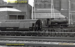 "Seen from a passing train a nicely clean LT 0-6-0PT, No. L92, sits outside the steam shed at Neasden depot, the power station filling the background. Nearer to camera is a converted ""Standard"" stock driving car, one of a batch that became ""Ballast Motor Cars"" service vehicles, L68 (?). Photo taken during 1966, but no actual date recorded!"