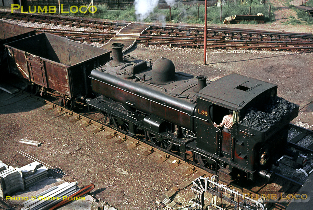 Ex-GWR 0-6-0PT No. 5764 is now London Transport No. L95, and is here arriving at Lillie Bridge Depot, seen from the West Cromwell Road bridge, with a train of empty wagons from Addison Road (now Kensington Olympia) on a lovely June day in 1969. Slide No.3809.