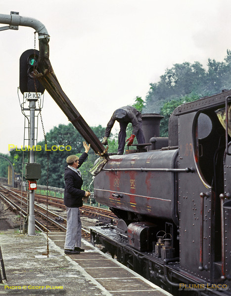 LT Pannier Tank No. L89 has arrived at Watford station to run-round its works train from Neasden and is now taking water from the tower on the end of the platform before returning to the tip at Croxley. September 1969. The water  tower was later dismantled and re-erected at the Buckinghamshire Railway Centre, Quainton Road. Slide No. 4079.