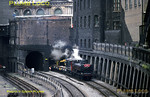 "Ex-GWR 57xx 0-6-0PT No. L94 (ex-7752) works ""The Last Steam Train on the Underground"", a demonstration works train here seen at Farringdon being stopped by signals on the ""Widened Lines"" from Moorgate, before getting the road again on its trip to Neasden Depot. This loco made it into preservation as 7752 at the Birmingham Railway Museum, Tyseley. Sunday 6th June 1971. Slide No. 7061."