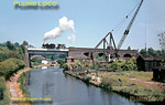 Ex-GWR 0-6-0PT, LT No. L89, has arrived at Watford with the spoil train from Neasden, it has run round and taken water and is now on its way back to the tip at Croxley. It is crossing the Grand Union canal just outside Watford station - a classic photographic location. The old canal wharf has fallen into disuse and disrepair, this was later swept away and a new leisure marina built in its place. June 1967. Slide No. 2808.