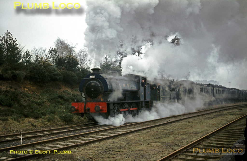 """LMR """"Austerity"""" 0-6-0ST No. AD196, with a train of ancient stock in tow, comes off the Hollywater line as it retraces its steps to Longmoor Downs station in appalling light! Saturday 16th April 1966. The number 68011 can just be seen painted on the smokebox door - it carried this identity for the filming of """"The Great St. Trinian's Train Robbery"""", made on location at the railway. Slide No. 1947."""