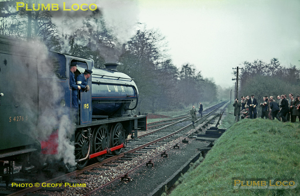 "After 2-10-0 No. AD600  ""Gordon"" worked the train from Woking to Liss main line station, ""Austerity"" 0-6-0ST No. AD (Army Department) 195 backed onto the stock of the RCTS ""Longmoor Military Railtour"" to take it through the exchange sidings onto LMR metals. The train then reversed again with ""Gordon"" leading into the LMR station at Liss, where No. 195 is seen prior to ""Gordon"" running round to double-head the train to Longmoor Downs. Saturday 16th April 1966. Slide No. 1942."