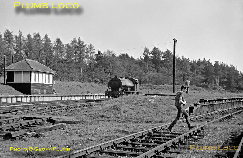 """""""Austerity"""" 0-6-0ST No. AD196 headed the RCTS """"Longmoor Military Railtour"""" from Longmoor Downs to Bordon with 2-10-0 """"Gordon"""" on the rear. As the LMR line curved through 180 degrees before entering Bordon station, this meant that """"Gordon"""" was on the right end of the train and facing the right way for departure from the adjacent former Southern Railway station. The tour train has now been shunted into the SR station and No. 196 makes its way from the bufferstops back towards Whitehill. Note the LMR signalbox on the platform. Saturday 30th April 1966."""