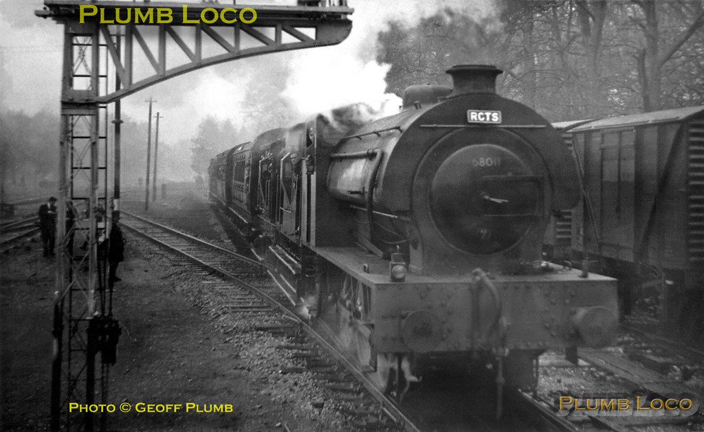 """With a wonderful train of ancient coaches (including a """"Birdcage"""" carriage) and brakevans, LMR """"Austerity"""" 0-6-0ST No. AD196 approaches Longmoor Downs station after traversing the Hollywater loop line with the first of two trains. The number 68011 was painted on the smokebox door during filming for """"The Great St. Trinian's Train Robbery"""". Scanned from a rather poor print taken in very poor light! Saturday 16th April 1966."""