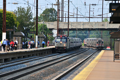 AEM-7 906 leads Amtrak 85 though Odenton past a load of commuters just discharged from MARC 440.