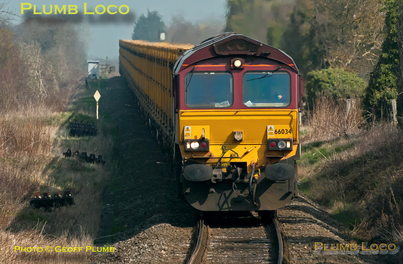 """66034 comes down the gradient towards the foot-crossing at Park Mill Farm, Princes Risborough, as it nears the junction with the main line. The train is 6A58, the 10:14 from Calvert to Northolt empty """"binliner"""" at 10:59 on a rather hazy Friday 23rd March 2012. Digital Image No. GMPI11318."""