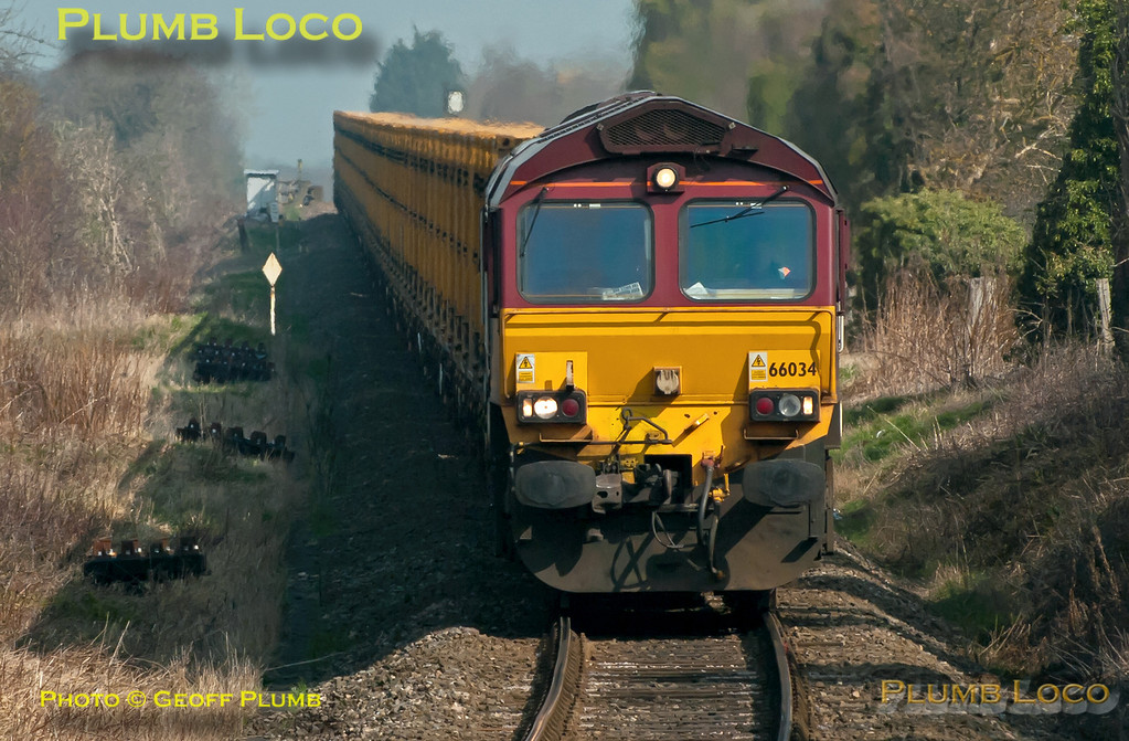 "66034 comes down the gradient towards the foot-crossing at Park Mill Farm, Princes Risborough, as it nears the junction with the main line. The train is 6A58, the 10:14 from Calvert to Northolt empty ""binliner"" at 10:59 on a rather hazy Friday 23rd March 2012. Digital Image No. GMPI11318."
