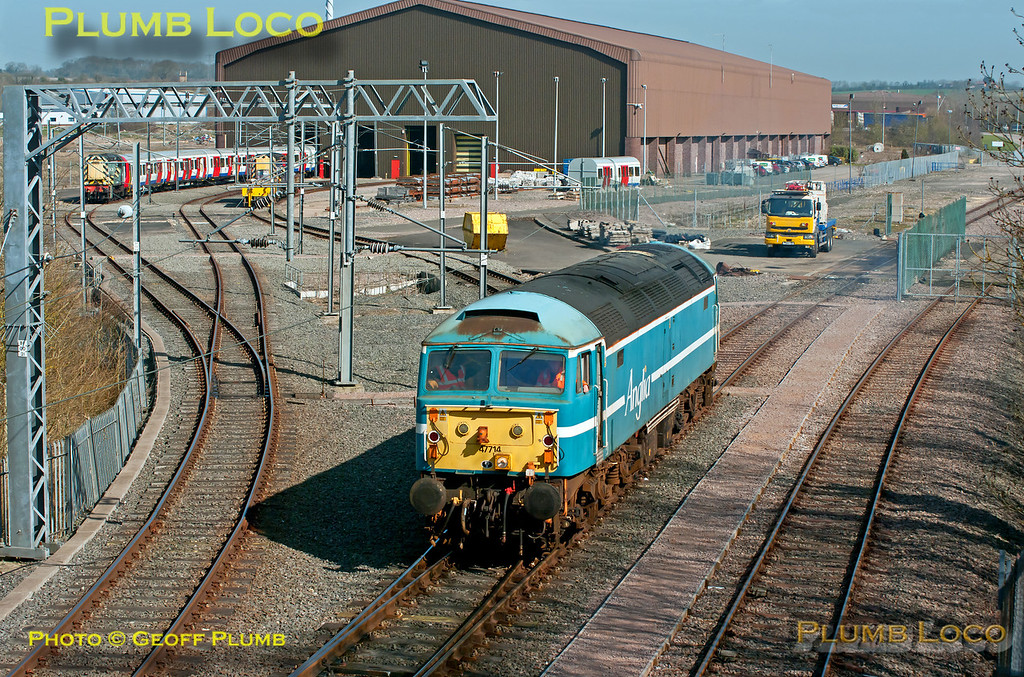 """A rather tatty looking 47714, in faded Anglia livery, departs light engine from the test depot at Asfordby, from where it took the test track northwards towards Old Dalby. On the left an 08 shunter is at the head of a set of LUL """"S"""" stock which has been undergoing tests and now awaits delivery. 11:31, Wednesday 28th March 2012. Digital Image No. GMPI11403."""