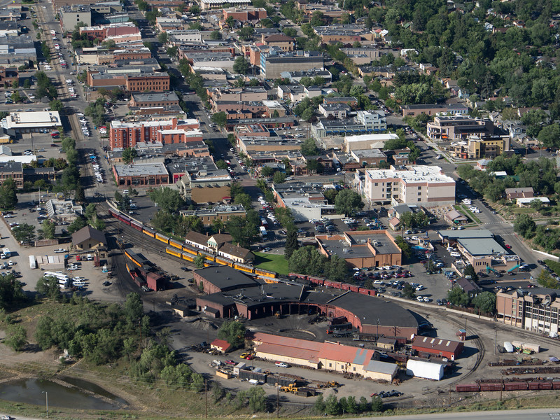 In this view from the slopes of nearby Smelter Mountain, the entirety of the Durango & Silverton's Durango facilities as well as most of downtown can be seen, as well as a glimpse of the Animas River at lower left.<br /> <br /> Prominent in the lower foreground is the D&S roundhouse and turntable.surrounded by the balloon track that is used to turn the trains each evening. The first of three daily trains has arrived from Silverton and is unloading at the depot (white with brown roof) which dates back to the arrival of the railroad in town back in 1881.<br /> <br /> Smelter Mountain is named for the industries that were located at its base back in the day....the main reason for Durango's economic existence. Today of course they are long gone. While the balloon track marks today's end of the line, originally the track extended off to the right, eventually reaching Chama, Antonito and Alamosa where one could change to standard gauge trains for Pueblo and Denver.<br /> <br /> August 2017