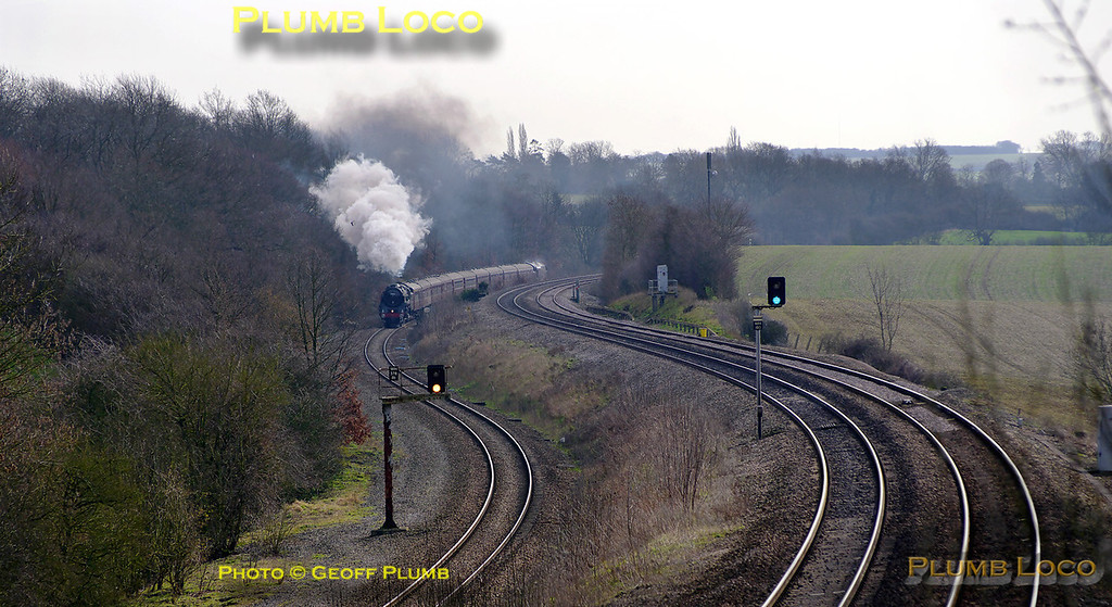 """On its first outing for some time after boiler repairs, """"Britannia"""" class 4-6-2 No. 70013 """"Oliver Cromwell"""" is hard at work on the climb to Sharnbrook summit as it approaches Souldrop with 37706 tagged on the back of the 10 coach train. This is 1Z48, """"The Lincoln Imp"""", 08:15 from London Victoria to Lincoln. It is running on time at 10:49 on what used to be the double track slow lines, now a single bi-directional line at this point. Saturday 12th March 2011. Digital Image No. GMPI8169."""
