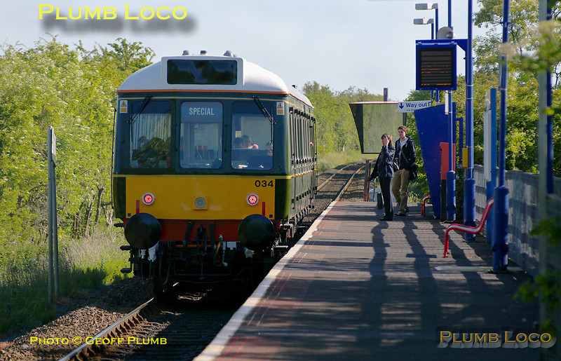 """A couple of passengers wait at Monks Risborough station as green """"bubblecar"""" 121 034 arrives with the 08:23 train from Princes Risborough to Aylesbury. This was its first day of revenue earning service, 08:26, Wednesday 25th May 2011. Digital Image No. GMPI9258."""