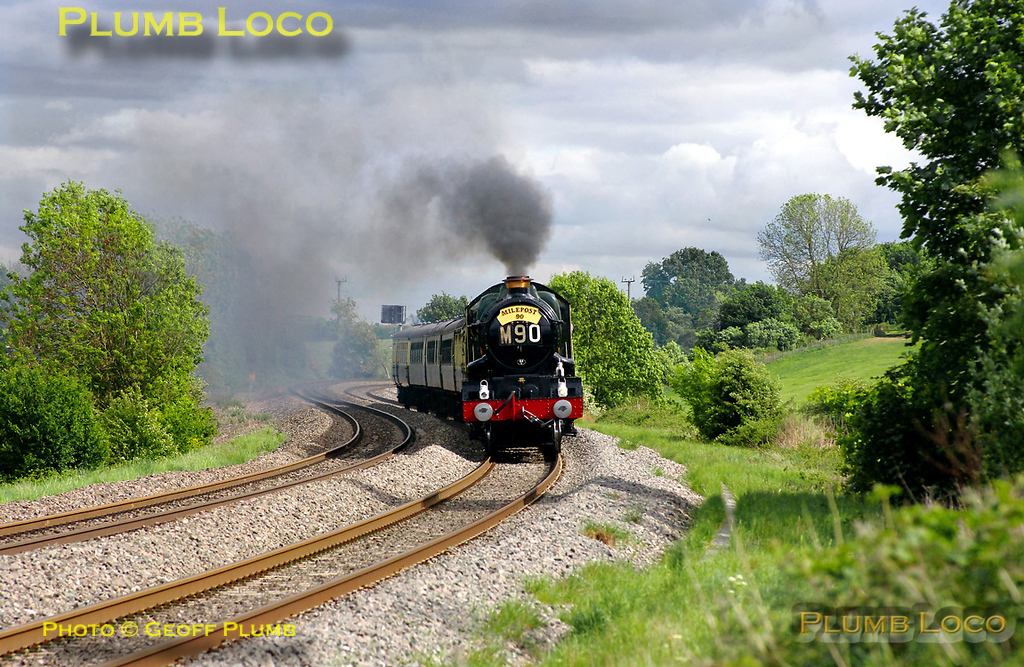 "Carrying the reporting number M90 and a ""Milepost 90"" headboard, GWR ""Castle"" 4-6-0 No. 5043 ""Earl of Mount Edgcumbe"" is simply flying along with the six coach private charter train, 1Z62. This was the return working, 15:50 from Oxford to Birmingham Moor Street (via Stratford-upon-Avon), presumably to celibrate someone's 90th birthday - and in some style too! The train was some five minutes early at this point and roaring up the gradient towards Fenny Compton as it approaches the foot-crossing at Clattercote, 16:21, Saturday 14th May 2011."