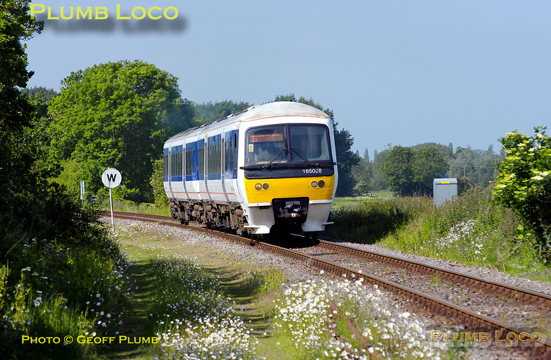 165 028 had the honour of forming the first train run by Chiltern Railways from Oxford to Bicester Town, on the first day the service was taken over by Chiltern from First Great Western, Sunday 22nd May 2011. This is the 09:36 from Oxford, approaching the level-crossing at Islip at 09:47, just before its first station stop at Islip, due 09:49. Digital Image No. GMPI9158.