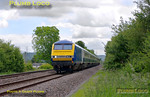 "5Z67 ran again on Friday 20th May 2011, but this time using the Chiltern ""hybrid"" set, AL02. Leaving Wembley LMD at 11:30 it is seen here passing the site of the old Ilmer Halt, between Princes Risborough and Haddenham, at 12:07, running a little early, en route to Hatton. Chiltern liveried DVT 82302 is at the head of the six coach mixed-livery set, with WSMR 67015 ""David J. Lloyd"" on the rear. Photo taken from a public footpath across the line. Digital Image No. GMPI9143."