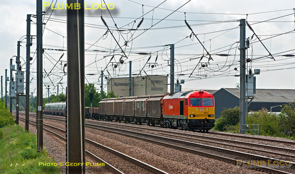 """Newly repainted 60015 in DBS red livery is at the head of 6Z30, the 08:47 from Dollands Moor to York National Railway Museum. It was dragging """"Javelin"""" unit No. 395 019 to York for display during """"Railfest"""", though the train has fifteen wagons between the loco and the unit for brake force. It has just passed Sandy at 12:54, a very awkward time of day on the ECML as the sun is straight down the track - though it had clouded over a little by this stage. Wednesday 30th May 2012. Digital Image No. GMPI12128."""