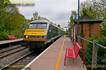 "Running a few minutes early, test train 5R00 draws into Denham Golf Club station where it stopped for power door testing. DVT 82305 leads the train, passing the old GWR ""Pagoda"" style platform shelter. The train departs Wembley LMD at 10:59 and stops at various intermediate stations en route to Birmingham Moor Street, including several that don't normally see loco-hauled sets stopping. 11:32, Thursday 17th May 2012. Digital Image No. GMPI11761."