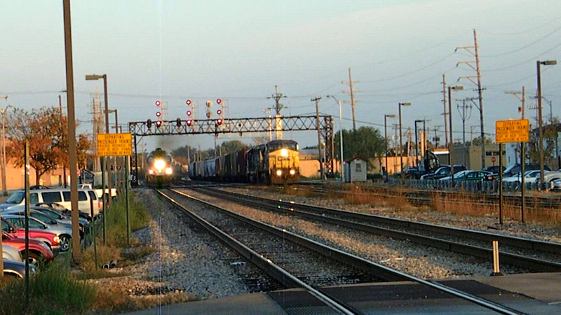 An outbound Metra rush hour express blows through Franklin Park, Illinois, as a CSX manifest freight continues plodding along on 10-12-10.