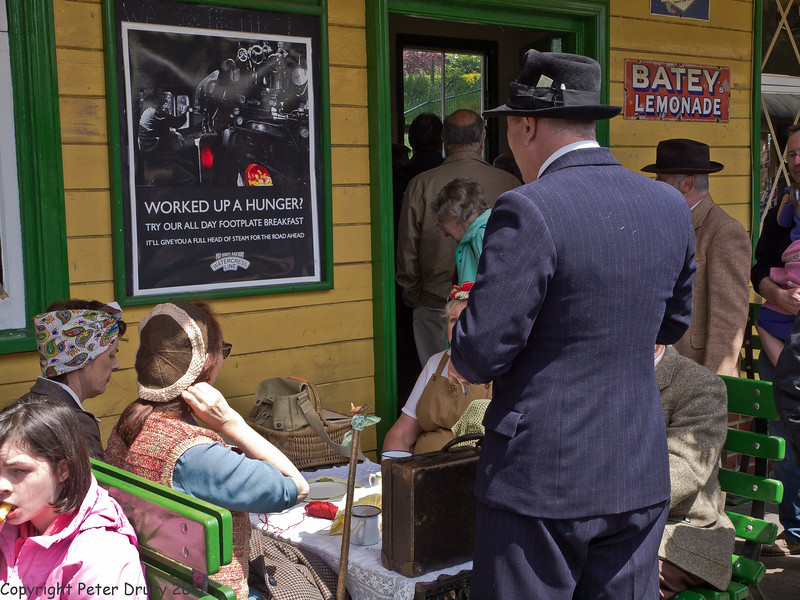 11 Jun 2011. War on the Line. Alresford Station Buffet. The gentleman, standing, is demonstrating a popular use at the time for his hat - a place to safely store the railway ticket. Copyright Peter Drury 2011